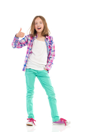 lumberjack shirt: Young girl in lumberjack shirt and green trousers showing thumb up and shouting. Full length studio shot isolated on white.