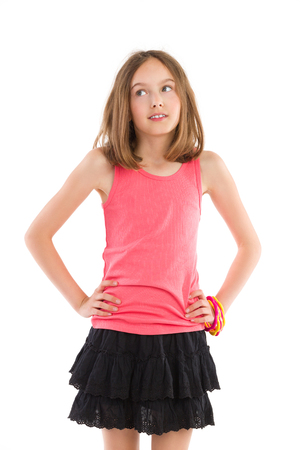 three quarter: Little girl posing with hands on hip and looking away. Three quarter length studio shot isolated on white.