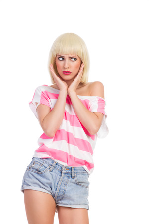 confused woman: Grimacing blond young woman in pink top and jeans shorts looking away. Three quarter length studio shot isolated on white.