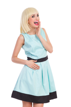 three quarter length: Fashionable blond female posing in blue dress, shouting and holding hand on chin. Three quarter length studio shot isolated on white.
