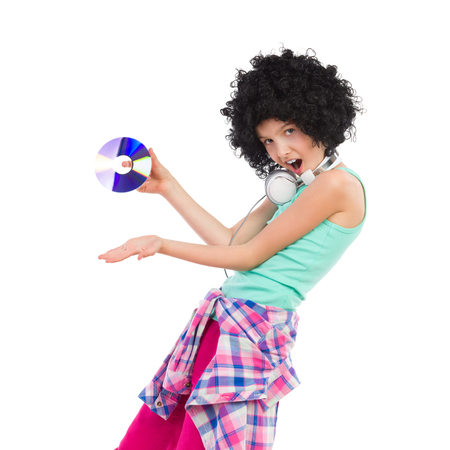 three quarter length: Little girl in afro wig presenting compact disc. Three quarter length studio shot isolated on white. Stock Photo
