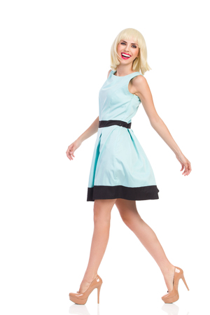 full shot: Elegance blond young woman walking and smiling at camera. Side view. Full length studio shot isolated on white.