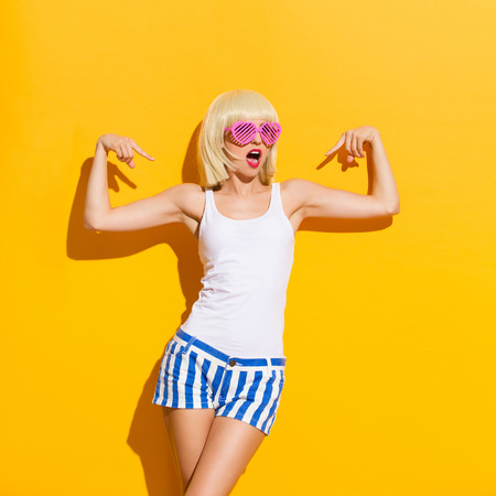 Blond young woman in pink sunglasses standing against yellow wall and pointing at herself. Three quarter length studio shot on yellow background.