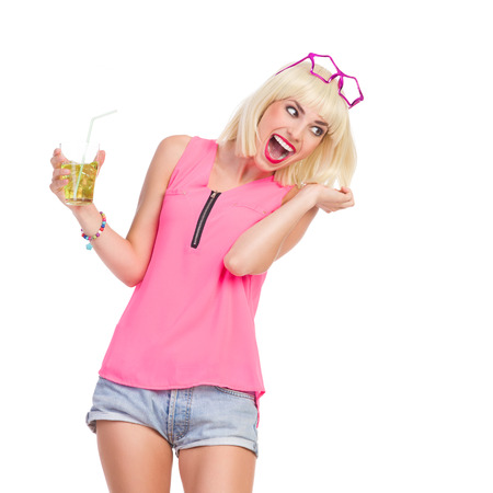 three quarter: Laughing blond young woman with drink. Three quarter length studio shot isolated on white.