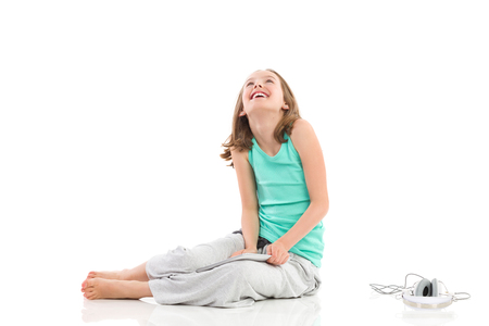 Smiling little girl sitting on the floor with digital tablet and headphones and looking up. Full length studio shot isolated on white. Stock Photo