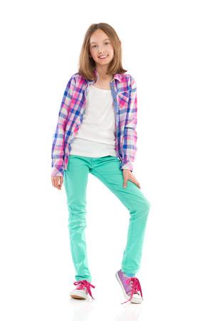 lumberjack shirt: Cheerful little girl posing in lumberjack shirt and green trousers. Full length studio shot isolated on white. Stock Photo