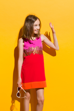 preadolescence: Fashionable girl in mini dress waving hand and looking away. Three quarter length studio shot on yellow background.