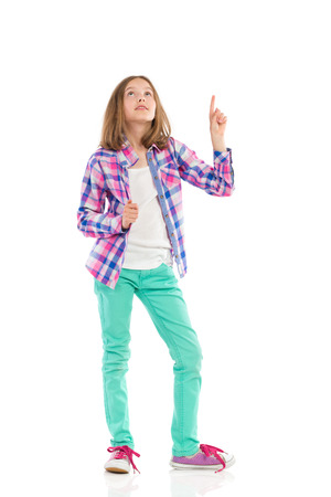 preadolescence: Little girl in lumberjack shirt pointing and looking up. Full length studio shot isolated on white.