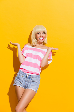 three quarter: Smiling blonde spread her hands and looking up. Three quarter length studio shot on yellow background. Stock Photo