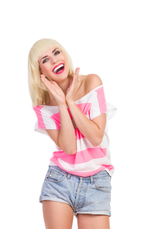 three quarter length: Laughing blond young woman in pink top and jeans shorts. Three quarter length studio shot isolated on white. Stock Photo