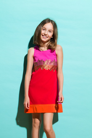 preadolescence: Cute fashionable little girl in red mini dress. Three quarter length studio shot on teal background.