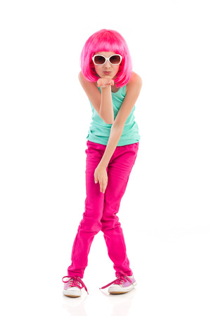preadolescence: Pink haired little girl in sunglasses blowing a kiss. Full length studio shot isolated on white.
