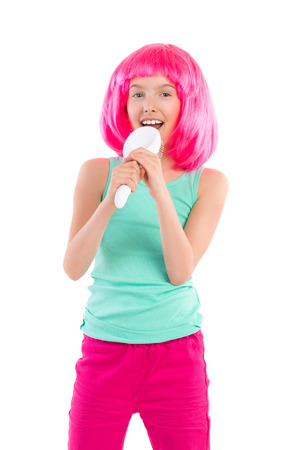 preadolescence: Little girl in pink wig singing to a hairbrush. Three quarter length studio shot isolated on white. Stock Photo
