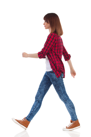 Woman in red lumberjack shirt, jeans and brown sneakers walking and looking away. Side view. Full length studio shot isolated on white. Stock Photo