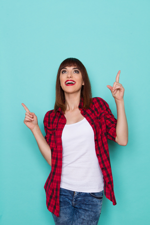 three quarter length: Smiling girl in red lumberjack shirt looking up and pointing. Three quarter length studio shot on turquoise background.