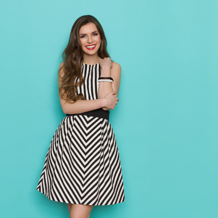 Smiling girl in black and white striped dress posing and looking at camera, Three quarter length studio shot on turquoise background.