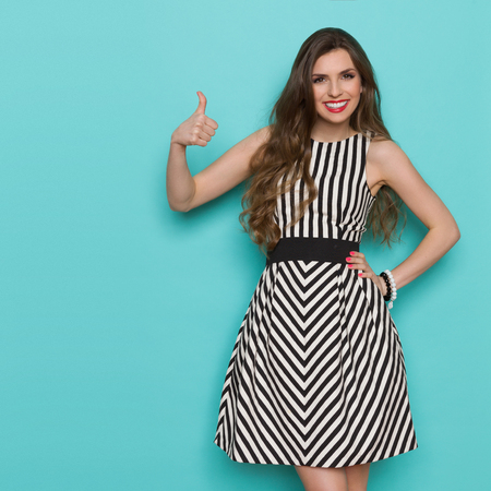 three quarter length: Smiling attractive woman in black and white striped dress showing thumb up and looking at camera, Three quarter length studio shot on teal background. Stock Photo