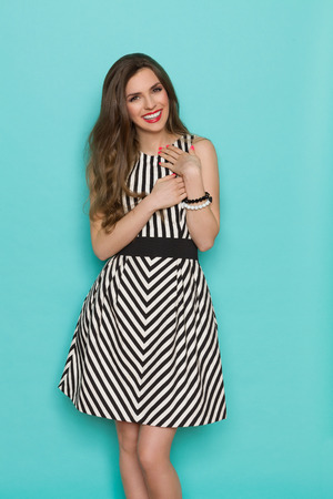 Smiling girl in black and white striped dress holding hands on her chest and looking at camera, Three quarter length studio shot on turquoise background. Standard-Bild