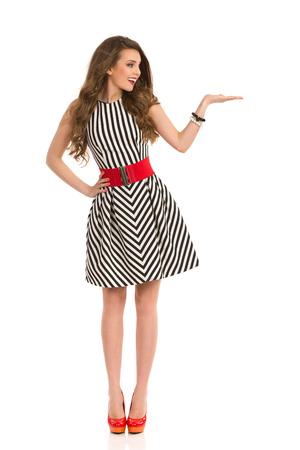 db106f3121  59445027 - Sonriente mujer atractiva en blanco y negro vestido de rayas y  tacones posando con la mano levantada