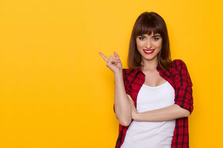 unbuttoned: Smiling young woman in unbuttoned red lumberjack shirt pointing away. Waist up studio shot on yellow background.
