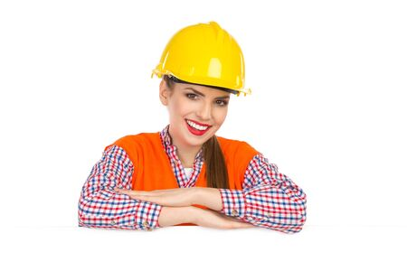 reflective vest: Beautiful smiling young woman in yellow hardhat, orange reflective vest and lumberjack shirt posing behind big white poster and looking at camera. Head and shoulders studio shot isolated on white.