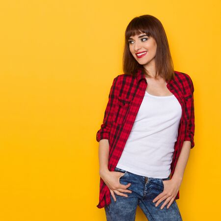 unbuttoned: Smiling young woman in unbuttoned red lumberjack shirt and jeans looking away. Three quarter length studio shot on yellow background.