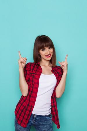 lumberjack shirt: Cheerful girl in red lumberjack shirt pointing up. Three quarter length studio shot on turquoise background. Stock Photo