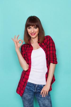 lumberjack shirt: Smiling young woman in red lumberjack shirt showing ok hand sign. Three quarter length studio shot on turquoise background. Stock Photo
