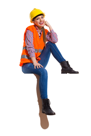 vest in isolated: Smiling young woman in yellow hardhat, orange reflective vest, lumberjack shirt, jeans and black boots, sitting relaxed on top and looking at camera. Full length studio shot isolated on white.