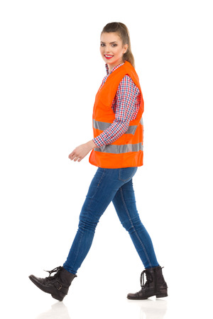 Young woman in orange reflective vest, lumberjack shirt, jeans, black boots, walking and looking at camera. Full length studio shot isolated on white. Stock Photo
