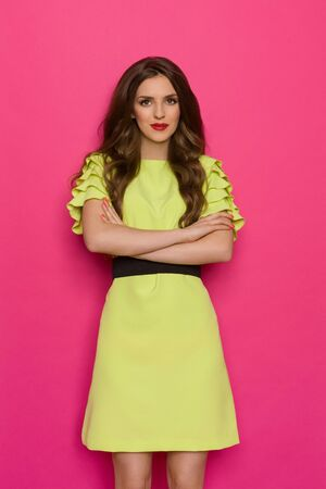 three quarter: Beautiful young woman in lime green dress posing with arms crossed. Three quarter length studio shot on yellow background.