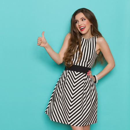 Shouting attractive woman in black and white striped dress showing thumb up and looking away, Three quarter length studio shot on teal background. Standard-Bild