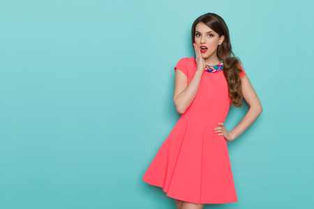 Surprised beautiful young woman in pink mini dress posing with hand on chin and looking at camera. Three quarter length studio shot on turquoise background. Standard-Bild