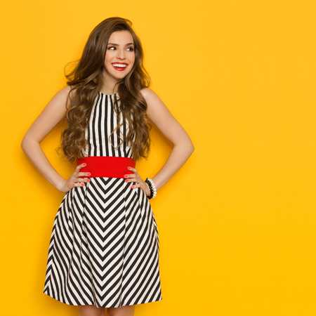 Smiling beautiful young woman in black and white striped dress posing with hands on hip and looking away. Three quarter length studio shot on yellow background.