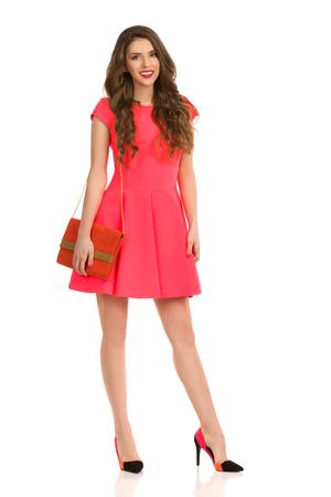 hermosa mujer joven y sonriente en vestido rosa y tacones altos posando con la corrección de color naranja longitud completa estudio aislado en blanco .