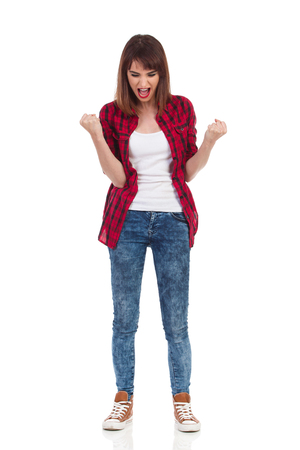 cheer full: Young woman in red lumberjack shirt, jeans and brown sneakers standing, looking down, clenching fists and shouting. Full length studio shot isolated on white.