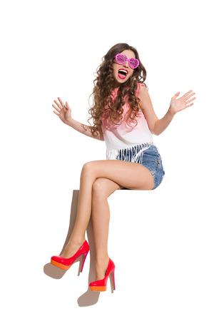 Mujer joven hermosa en tapa rosada, pantalones cortos, en forma de corazón rosa gafas de sol y tacones altos, sentado con las piernas cruzadas sobre la parte superior de la bandera blanca y gritando. Estudio de longitud completa aislado disparo en blanco. Foto de archivo
