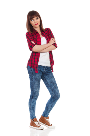 waiting glance: Young woman in red lumberjack shirt, jeans and brown sneakers standing with arms crossed and looking away. Full length studio shot isolated on white. Stock Photo