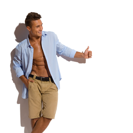 Handsome young man in beige shorts and blue unbuttoned shirt standing relaxed against sunny wall and looking away and showing thumb up. Three quarter length studio shot on white background Stock Photo