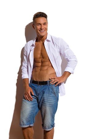 unbuttoned: Handsome young man in jeans shorts and white unbuttoned shirt standing relaxed against sunny wall and looking at camera. Three quarter length studio shot on white background