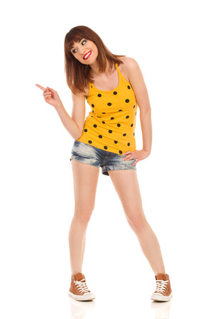 legs apart: Young woman in yellow dotted shirt, jeans shorts and brown sneakers standing legs apart and pointing. Full length studio shot isolated on white.