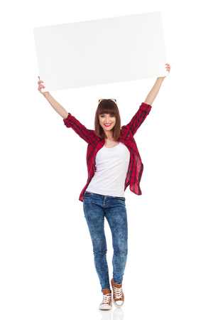 white poster: Smiling attractive woman in red lumberjack shirt, jeans and brown sneakers standing and holding big white poster above her head. Full length studio shot isolated on white.