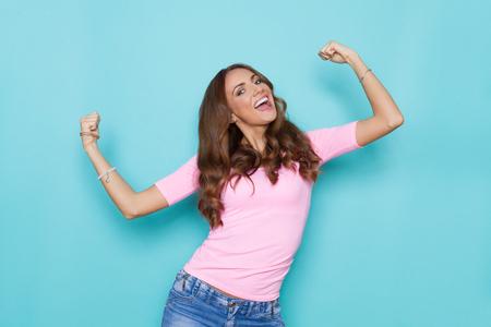 Bonne belle jeune femme en chemise rose pastel qui crie et fléchit les muscles. Tirage du studio de taille sur fond turquoise.