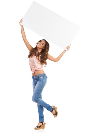 big cork: Smiling attractive woman in pink shirt, jeans, and cork high heels, standing on one leg and holding big white poster above her head. Full length studio shot isolated on white.