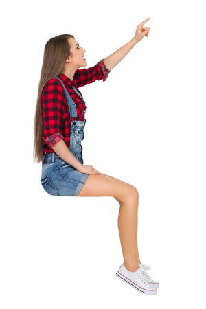 dungarees: Happy young woman in red lumberjack shirt, jeans dungarees shorts and white sneakers sitting, pointing up and looking away. Three quarter length studio shot isolated on white.