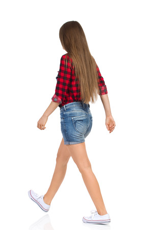 striding: Walking woman in red lumberjack shirt, jeans shorts and white sneakers. Rear view. Full length studio shot isolated on white. Stock Photo