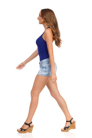 Walking smiling girl in blue shirt, jeans shorts and cork heels. Full length studio shot isolated on white. Stock Photo