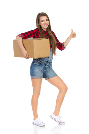 dungarees: Happy young woman in red lumberjack shirt, jeans dungarees shorts, and white sneakers, holding box under her arm and showing thumb up. Full length studio shot isolated on white.