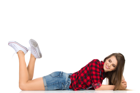 lumberjack shirt: Smiling young woman in red lumberjack shirt, jeans shorts and white sneakers lying down on a floor and looking away. Full length studio shot isolated on white.