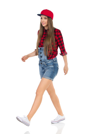 Woman in red lumberjack shirt, jeans shorts white sneakers and full cap walking and looking away. Side, front view. Full length studio shot isolated on white. Stock Photo